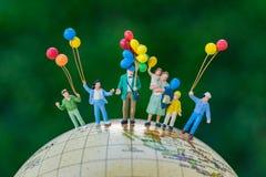 οι μικροσκοπικοί άνθρωποι λογαριάζουν τα ευτυχή μπαλόνια οικογενειακής εκμετάλλευσης που στέκονται το ο Στοκ Φωτογραφίες