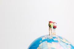 Οι μικροσκοπικοί άνθρωποι λογαριάζουν τη στάση στον παγκόσμιο χάρτη σφαιρών Στοκ Φωτογραφία