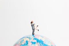 Οι μικροσκοπικοί άνθρωποι λογαριάζουν τη στάση στον παγκόσμιο χάρτη σφαιρών Στοκ Εικόνες
