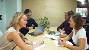 Οι μοντέρνοι άνθρωποι που κάθονται στη διάσκεψη παρουσιάζουν και δραστήρια που συζητούν τα καθημερινά επιχειρηματικά σχέδια φιλμ μικρού μήκους