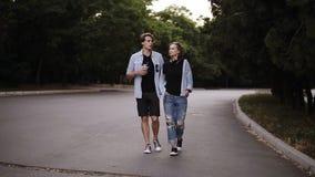 Οι μοντέρνοι νέοι περπατούν από το πράσινο πάρκο με τα δέντρα και την ομιλία Φθορά των περιστασιακών καθιερωνόντων τη μόδα ενδυμά φιλμ μικρού μήκους