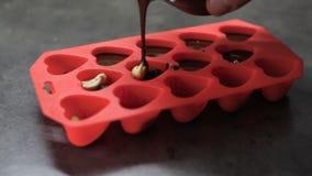 Οι μορφές υπό μορφή καρδιών χύνονται με τη λειωμένη σοκολάτα απόθεμα βίντεο