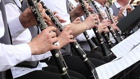 Οι μουσικοί ατόμων παίζουν τα κλαρινέτα στη δημοτική ορχήστρα αποδίδοντας στη συναυλία υπαίθρια φιλμ μικρού μήκους