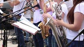 Οι μουσικοί γυναικών παίζουν saxophones στη δημοτική ορχήστρα αποδίδοντας στη συναυλία υπαίθρια απόθεμα βίντεο