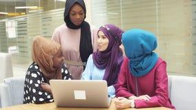 Οι μουσουλμανικές ασιατικές και αφρικανικές γυναίκες στα hijabs κάθονται στους καφέδες και κάνουν τις σε απευθείας σύνδεση αγορές απόθεμα βίντεο