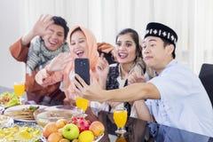Οι μουσουλμανικοί λαοί κάνουν μια τηλεοπτική κλήση με ένα τηλέφωνο στοκ εικόνες