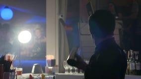 Οι μπάρμαν παρουσιάζουν, ο μπάρμαν κάνει τα τεχνάσματα με ένα μπουκάλι και έναν δονητή πίσω από τη στάση φραγμών στο νυχτερινό κέ απόθεμα βίντεο