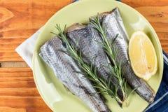 Οι μπακαλιάροι αλιεύουν με το δεντρολίβανο και το λεμόνι στο πράσινο πιάτο επάνω από τον ξύλινο πίνακα Στοκ Εικόνες