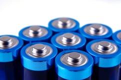 Οι μπλε-μπλε μπαταρίες AA κλείνουν επάνω σε ένα άσπρο υπόβαθρο Ρηχό βάθος του τομέα, μακροεντολή στοκ φωτογραφία