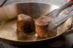 Οι μπριζόλες βόειου κρέατος είναι τηγανισμένες σε ένα τηγανίζοντας τηγάνι σε ένα εστιατόριο στοκ εικόνες