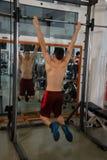 Οι νέες αρσενικές ασκήσεις στη γυμναστική χρησιμοποιούν το multipower στοκ εικόνες