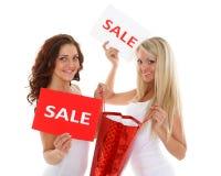 Οι νέες γυναίκες με την πώληση υπογράφουν. στοκ φωτογραφία με δικαίωμα ελεύθερης χρήσης