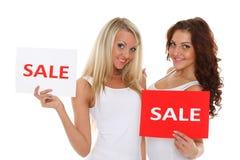 Οι νέες γυναίκες με την πώληση υπογράφουν. στοκ φωτογραφίες