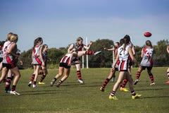 Οι νέες γυναίκες παίζουν το αυστραλιανό ποδόσφαιρο κανόνων Στοκ Φωτογραφίες