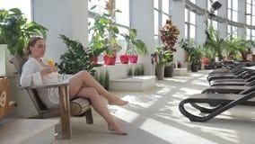 Οι νέες γυναίκες που χαλαρώνουν στη φωτεινή εσωτερική στοά luxury spa στο σαλόνι απόθεμα βίντεο