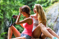 Οι νέες γυναίκες στηρίζονται στους βράχους στον καταρράκτη ζουγκλών στο υπόβαθρο Στοκ Φωτογραφίες