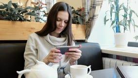 Οι νέες εικόνες brunette γυναικών teapot και του φλυτζανιού σε έναν καφέ στο κύτταρό της τηλεφωνούν απόθεμα βίντεο