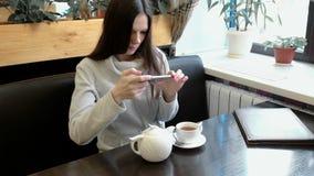Οι νέες εικόνες brunette γυναικών teapot και του φλυτζανιού σε έναν καφέ στο κύτταρό της τηλεφωνούν Μπροστινή όψη απόθεμα βίντεο