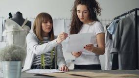 Οι νέες ελκυστικές γυναίκες εξετάζουν το ένδυμα που σύρει και που συζητά το εργαζόμενες στο σύγχρονο ράβοντας στούντιο φιλμ μικρού μήκους