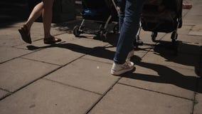 Οι νέες ευτυχείς γυναίκες μητέρων με τους περιπατητές μωρών περπατούν κάτω από τον ομιλούντα περίπατο οδών φιλμ μικρού μήκους