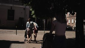 Οι νέες ευτυχείς γυναίκες μητέρων με τους περιπατητές μωρών περπατούν κάτω από τον ομιλούντα περίπατο οδών απόθεμα βίντεο