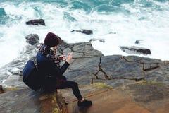 Οι νέες μοντέρνες θηλυκές φωτογραφίες προσοχής στο κύτταρο τηλεφωνούν καθμένος σε έναν βράχο κοντά στον ωκεανό στοκ εικόνα
