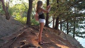 Οι νέες στάσεις γυναικών σε μια γραφική θέση στην παραλία, κάνουν τη φωτογραφία στο τηλέφωνο απόθεμα βίντεο