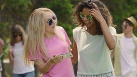 Οι νέες όμορφες γυναίκες που βλέπουν τις φωτογραφίες στο smartphone στο πάρκο, κόμμα, χαλαρώνουν φιλμ μικρού μήκους