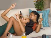 Οι νέες όμορφες και ευτυχείς ασιατικές φίλες συνδέουν ή αδελφές που απολαμβάνουν τα κοινωνικά μέσα Διαδικτύου που έχουν τη διασκέ στοκ φωτογραφίες