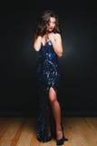 Οι νέες όμορφες σγουρές γυναίκες ακτινοβολούν μέσα φόρεμα στο σκοτεινό υπόβαθρο Copyspace Εορτασμός έννοιας στοκ φωτογραφίες