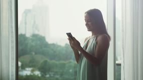 Οι νέες όμορφες χρήσεις επιχειρηματιών του κινητού τηλεφώνου υπερασπίζονται το πανοραμικό παράθυρο με την άποψη πόλεων 3840x2160 απόθεμα βίντεο