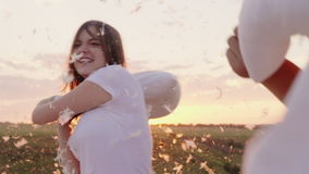 Οι νέοι έχουν τρελλά τη διασκέδαση Μια γυναίκα κτυπά το μαξιλάρι της με έναν φίλο, τα φτερά πετούν Πάλη ενάντια απόθεμα βίντεο