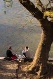 Οι νέοι απολαμβάνουν τη ζεστασιά της άνοιξη, καθμένος στις τράπεζες του Σηκουάνα στο Παρίσι Στοκ Φωτογραφίες