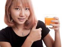 Οι νέοι ασιατικοί αντίχειρες γυναικών επάνω πίνουν το χυμό από πορτοκάλι Στοκ φωτογραφία με δικαίωμα ελεύθερης χρήσης