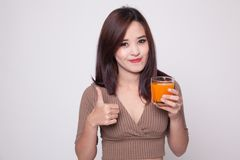 Οι νέοι ασιατικοί αντίχειρες γυναικών επάνω πίνουν το χυμό από πορτοκάλι Στοκ Φωτογραφίες
