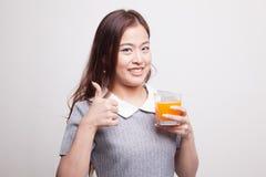 Οι νέοι ασιατικοί αντίχειρες γυναικών επάνω πίνουν το χυμό από πορτοκάλι Στοκ εικόνες με δικαίωμα ελεύθερης χρήσης