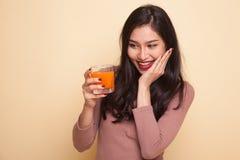 Οι νέοι ασιατικοί αντίχειρες γυναικών επάνω πίνουν το χυμό από πορτοκάλι Στοκ Εικόνες