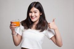 Οι νέοι ασιατικοί αντίχειρες γυναικών επάνω πίνουν το χυμό από πορτοκάλι Στοκ Φωτογραφία