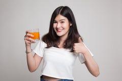 Οι νέοι ασιατικοί αντίχειρες γυναικών επάνω πίνουν το χυμό από πορτοκάλι Στοκ Εικόνα