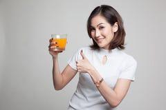 Οι νέοι ασιατικοί αντίχειρες γυναικών επάνω πίνουν το χυμό από πορτοκάλι Στοκ εικόνα με δικαίωμα ελεύθερης χρήσης