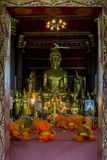 Οι νέοι βουδιστικοί μοναχοί προσεύχονται μέσα σε έναν ναό σε Luang Prabang, Λάος στοκ εικόνα