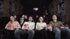 Οι νέοι γελούν στον κινηματογράφο κωμωδίας στο θέατρο κινηματογράφων Νέοι που γελούν στη διασκεδάζοντας κωμωδία προσοχής κινηματο απόθεμα βίντεο