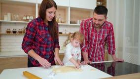 Οι νέοι γονείς βοηθούν την κόρη μικρών παιδιών τους για να αποκόψουν τα μπισκότα απόθεμα βίντεο