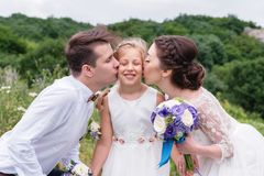 Οι νέοι γονείς στα γαμήλια φορέματα φιλούν τη νέα κόρη τους στα μάγουλα στοκ εικόνες