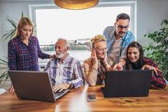 Οι νέοι εθελοντές βοηθούν τους ανώτερους ανθρώπους στον υπολογιστή στοκ εικόνα