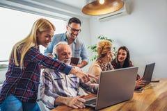 Οι νέοι εθελοντές βοηθούν τους ανώτερους ανθρώπους στον υπολογιστή στοκ φωτογραφία με δικαίωμα ελεύθερης χρήσης