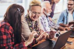 Οι νέοι εθελοντές βοηθούν τους ανώτερους ανθρώπους στον υπολογιστή στοκ φωτογραφίες