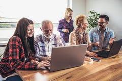 Οι νέοι εθελοντές βοηθούν τους ανώτερους ανθρώπους στον υπολογιστή στοκ φωτογραφίες με δικαίωμα ελεύθερης χρήσης