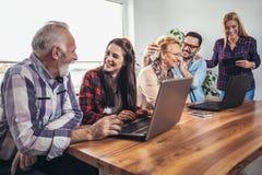 Οι νέοι εθελοντές βοηθούν τους ανώτερους ανθρώπους στον υπολογιστή στοκ εικόνες
