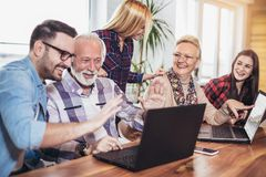 Οι νέοι εθελοντές βοηθούν τους ανώτερους ανθρώπους στον υπολογιστή στοκ φωτογραφία